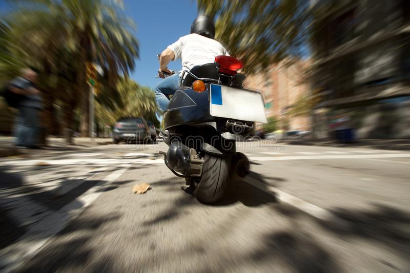 Rear view of man with helmet riding a scooter fast on city street with speed blur effect royalty free stock image