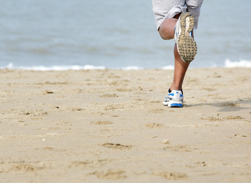 Rear View Of Man Jogging At The Beach Stock Photo