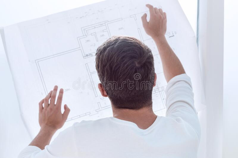 Rear view. man looking at blank drawing sheet. Photo with copy space royalty free stock images