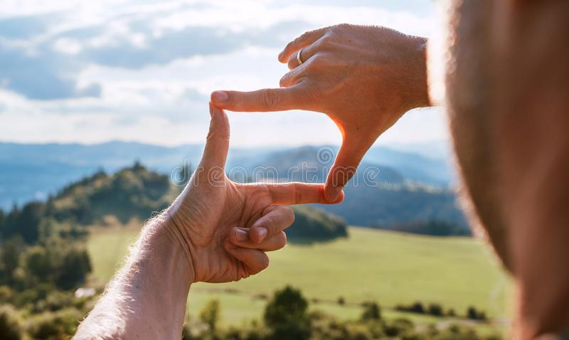 Rear view of Man looking at mountain landscape framing with fingers, searching for best image composition as he hiking over the stock images