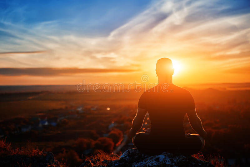 Rear view of the man meditating yoga in lotus pose on the rock at sunset. Horizontal photo. Beautiful landscape with sky and clouds like a background. Concept stock photo