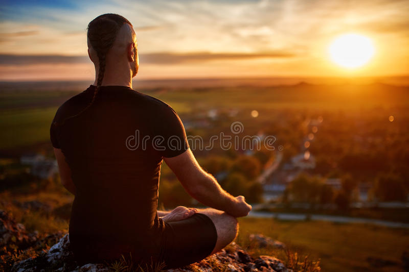 Rear view of the man meditating yoga in lotus pose on the rock at sunset. Horizontal photo. Beautiful landscape with sky and clouds like a background. Concept stock photography