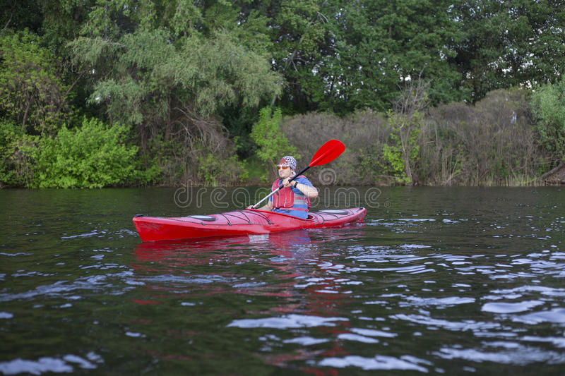Rear view of man paddling kayak in lake with woman in background. Couple kayaking in lake on a sunny day. stock photography