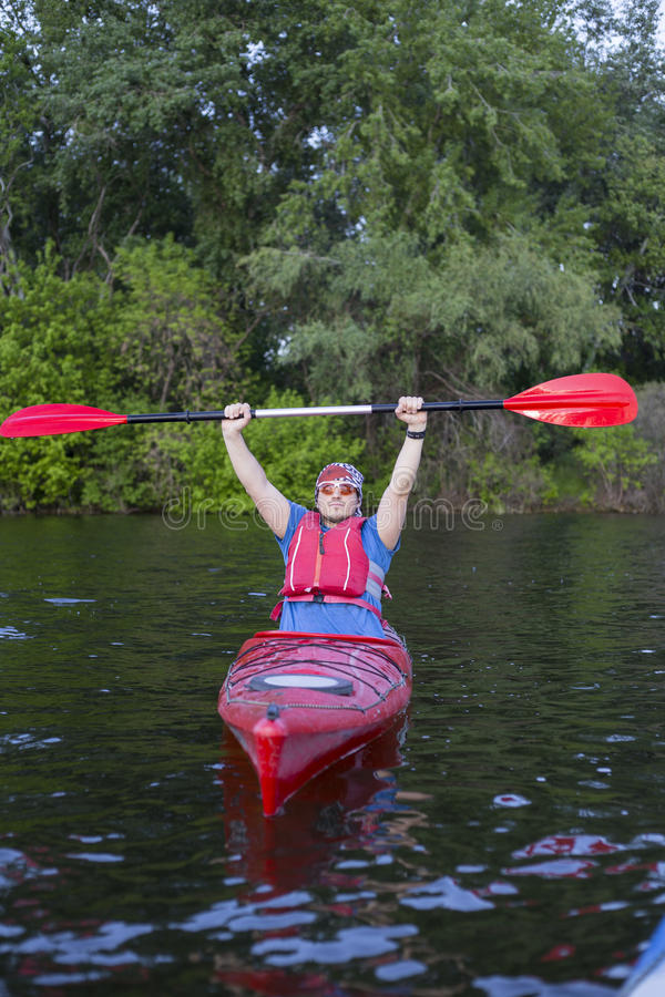 Rear view of man paddling kayak in lake with woman in background. Couple kayaking in lake on a sunny day. stock photo