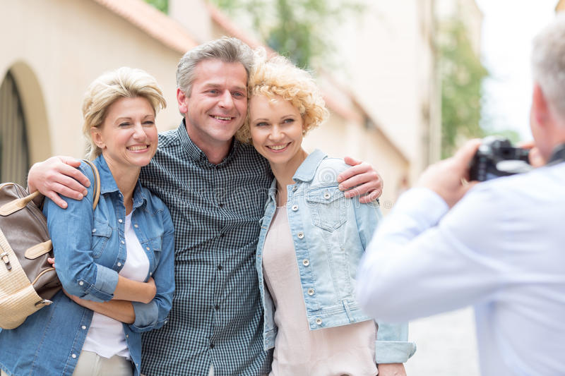 Rear view of man photographing male and female friends in city royalty free stock photo