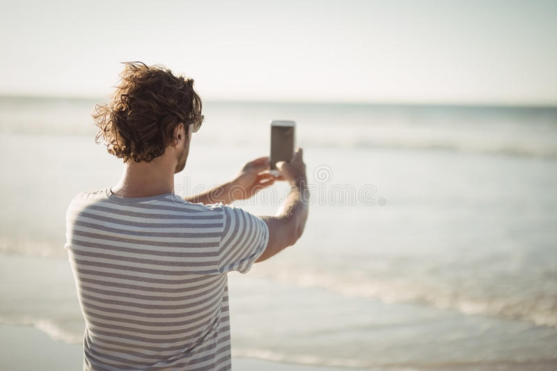 Rear view of man photographing sea at beach royalty free stock images