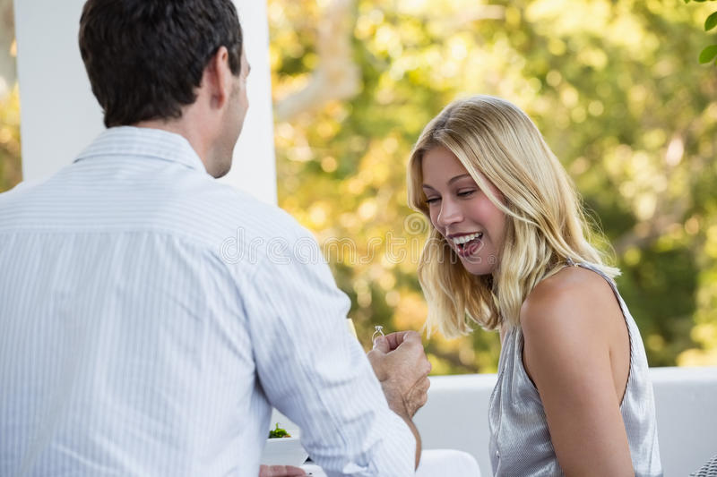 Rear view of man proposing happy young woman. Rear view of men proposing happy young women at restaurant stock photos