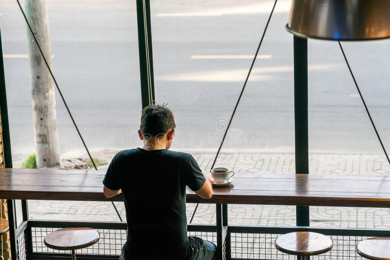 Rear view of man reading book in a cafe royalty free stock photo