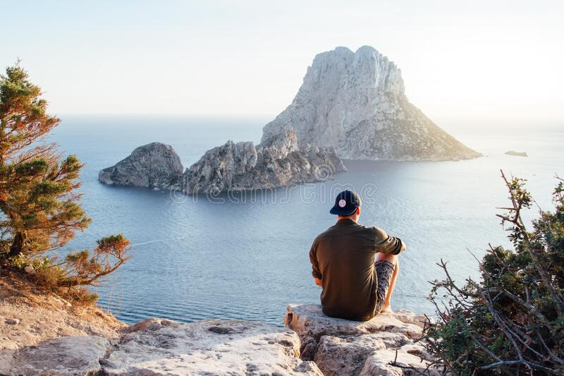 Rear View of Man Sitting on Rock by Sea stock photos