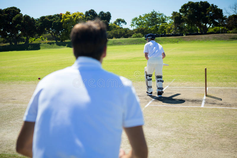 Rear view of man standing by batsman at cricket field royalty free stock image