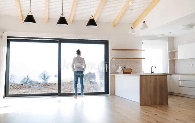 Rear view of man standing in unfurnished house, moving in new home concept. royalty free stock photos