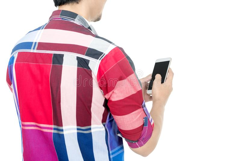 Rear view of man touch the mobile phone screen. Posing isolated over white background royalty free stock photography