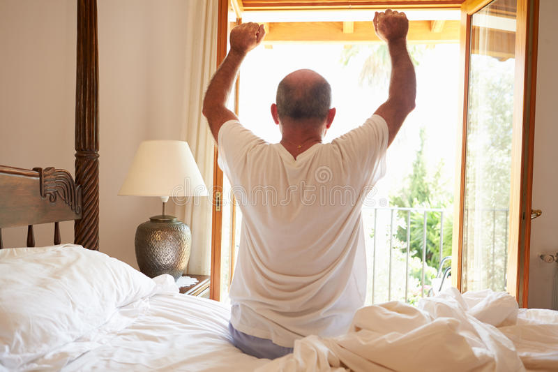 Rear View Of Man Waking Up In Bed In Morning royalty free stock photos