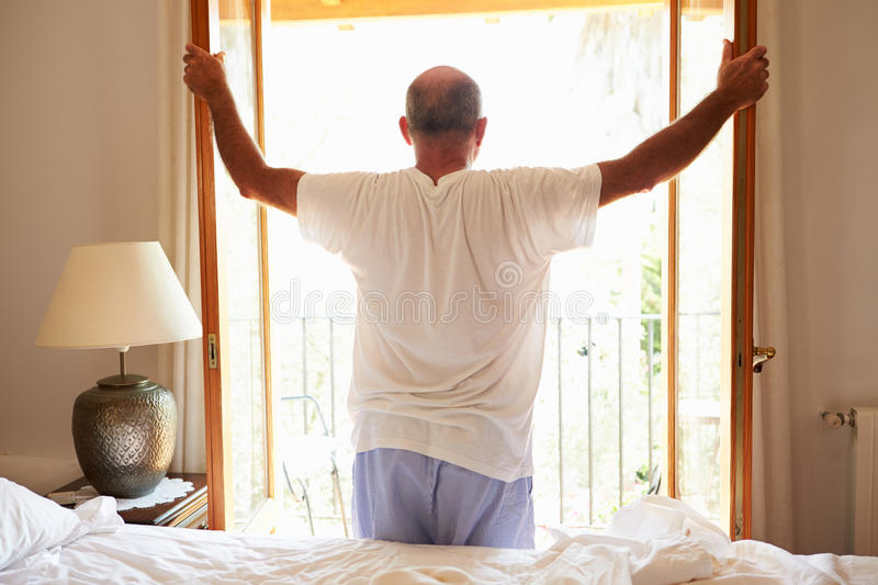 Rear View Of Man Waking Up In Bed In Morning stock photography