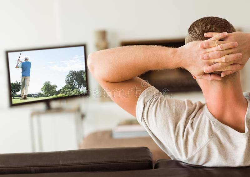Rear view of man watching television in living room royalty free stock images
