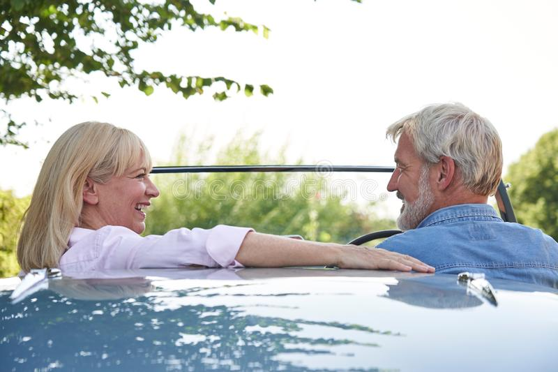 Rear View Of Mature Couple Enjoying Road Trip In Classic Open Top Sports Car Together stock image