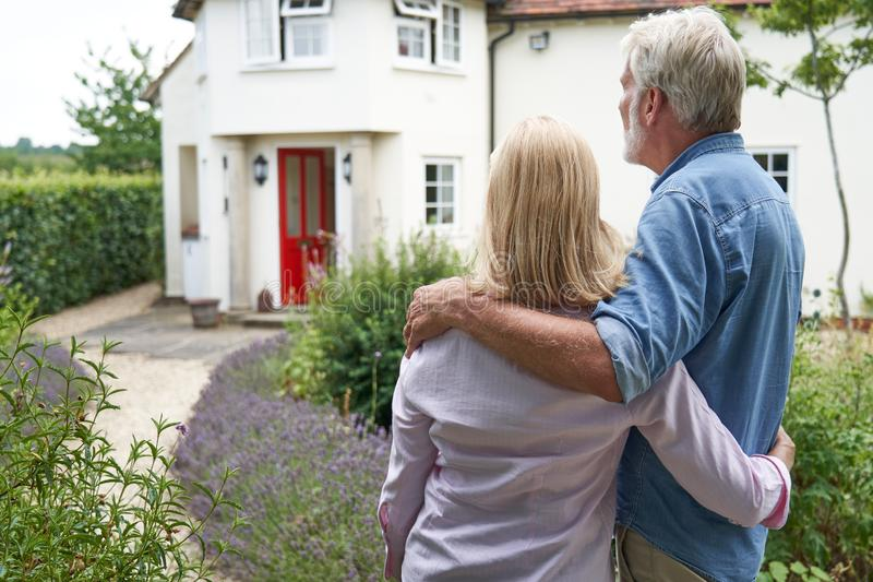 Rear View Of Mature Couple Standing In Garden Look At Dream Home In Countryside stock images