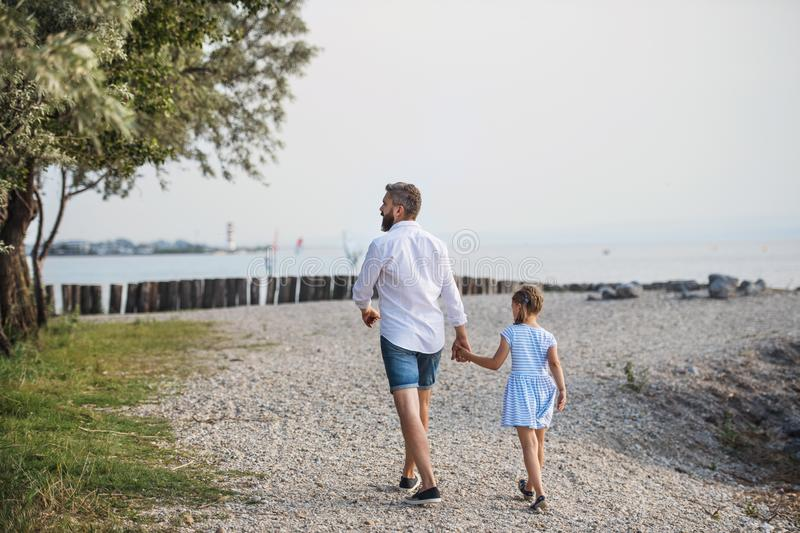 Rear view of mature father walking with small daughter on a holiday by the lake. stock photos