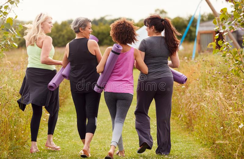 Rear View Of Mature Female Friends On Outdoor Yoga Retreat Walking Along Path Through Campsite stock images