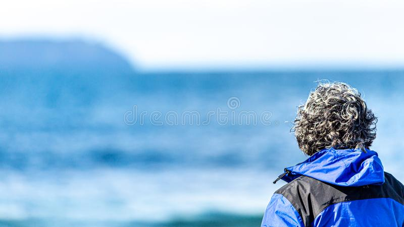 Rear view of a mature woman with gray hair looking at the sea. With a blue blurred in the background, wonderful sunny day in Ireland royalty free stock photos