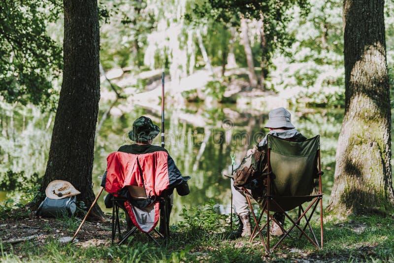 Rear view of men enjoying fishing on the river bank stock image