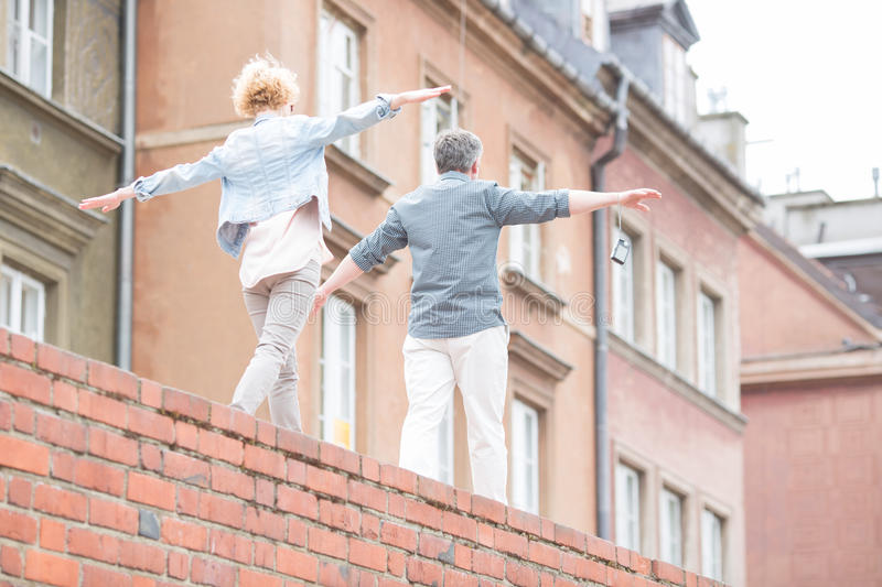 Rear view of middle-aged couple with arms outstretched walking on brick wall stock photos