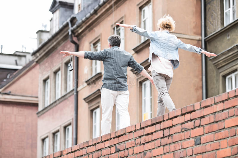 Rear view of middle-aged couple with arms outstretched walking on brick wall royalty free stock images