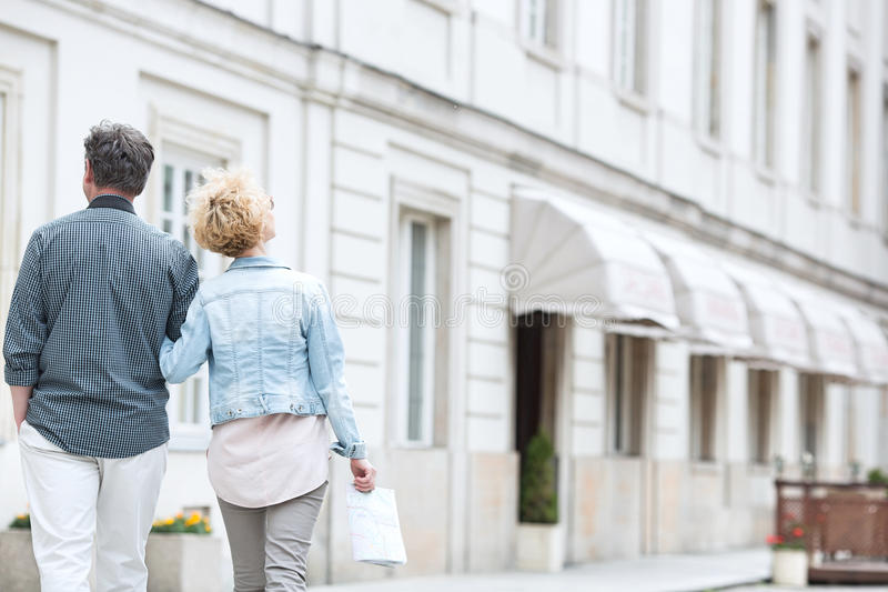 Rear view of middle-aged couple walking by building stock photography