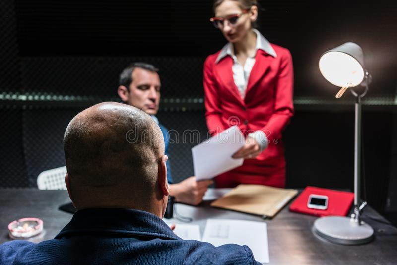 Suspect or witness during police interrogation. Rear view of a middle-aged suspect or witness sitting at desk during the police interrogation in front of the royalty free stock image