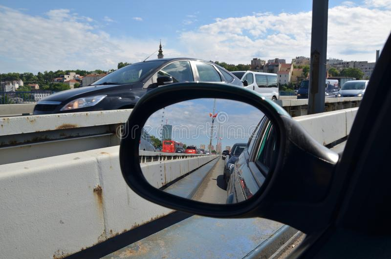 City traffic in rear view mirror stock image
