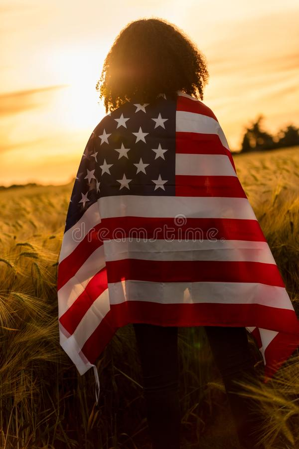 Girl TeenagerFemale Young Woman Wrapped in USA Flag in Field at Sunset royalty free stock photos