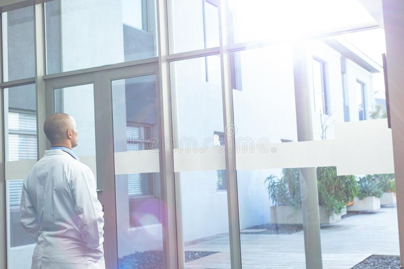 Male doctor with hands in pocket looking through window in hospital. Rear view of Mixed-race male doctor with hands in pocket looking through window in lobby of stock photos