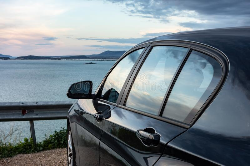 Rear view of modern luxury black car parked above the sea with a romantic view during the sunset royalty free stock image