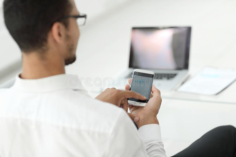 Rear view. modern man browsing media files on his smartphone stock photography
