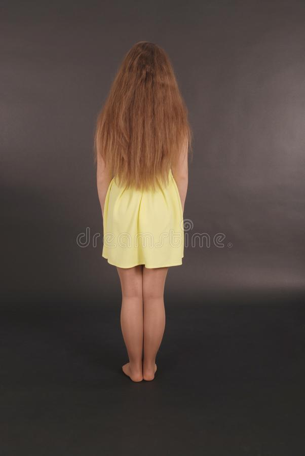 Rear view of modern young girl, standing. On black background royalty free stock image
