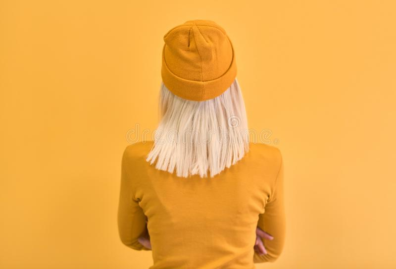 Rear view monochrome portrait of pretty blonde hair woman wearing yellow clothes, with crossed hands, looking at blank wall with stock photography