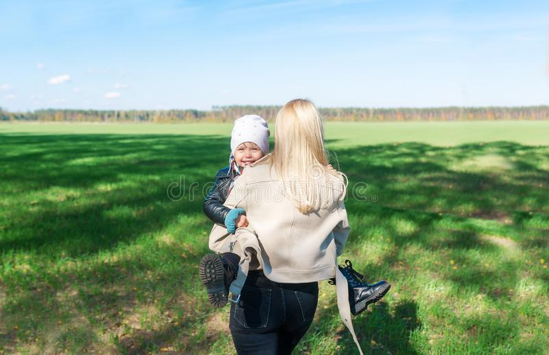 Rear view of mother and baby daughter walking in green meadow royalty free stock photo