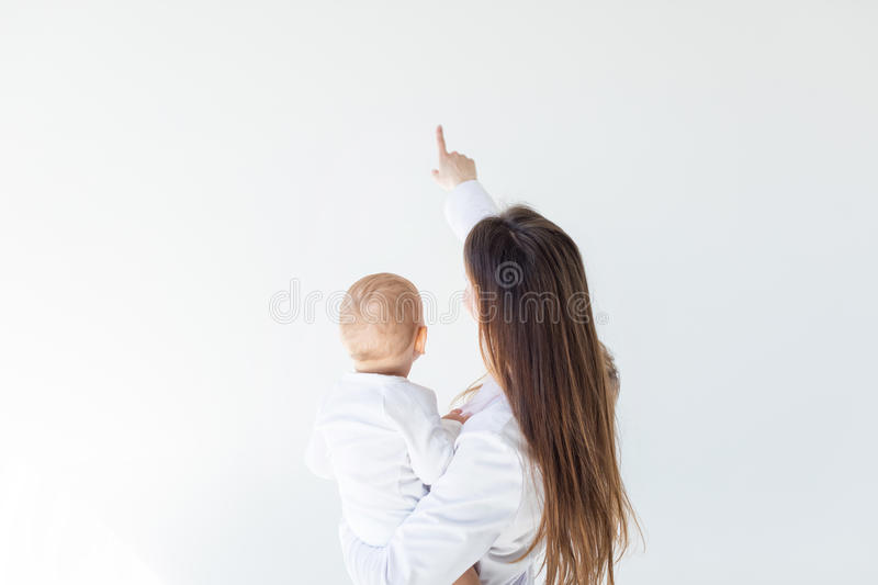Rear view of mother holding adorable baby boy and pointing isolated on white stock image