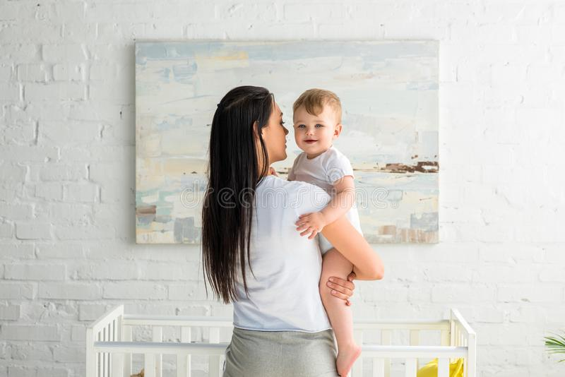 rear view of mother holding cute smiling baby in hands stock photo