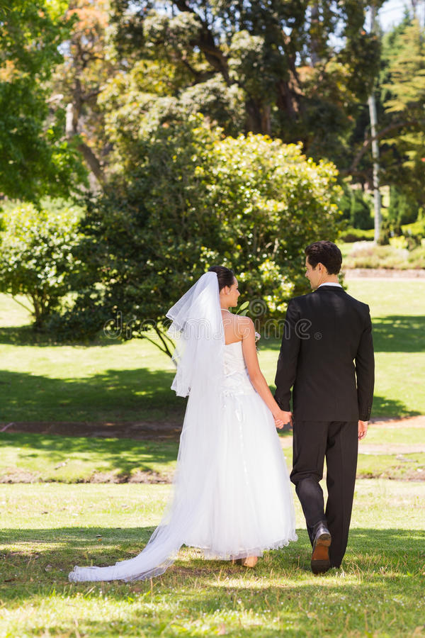 Rear view of newlywed couple walking in park royalty free stock photos