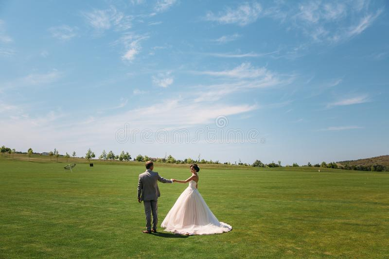 Rear view, newlyweds are walking along the green field of the golf club on a wedding day. The bride and groom in wedding. Dresses are holding hands. Man in a royalty free stock images