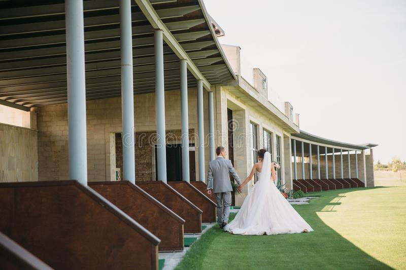 Rear view, newlyweds are walking along the green field of the golf club on a wedding day. The bride and groom in wedding. Dresses are holding hands. Man in a royalty free stock photography