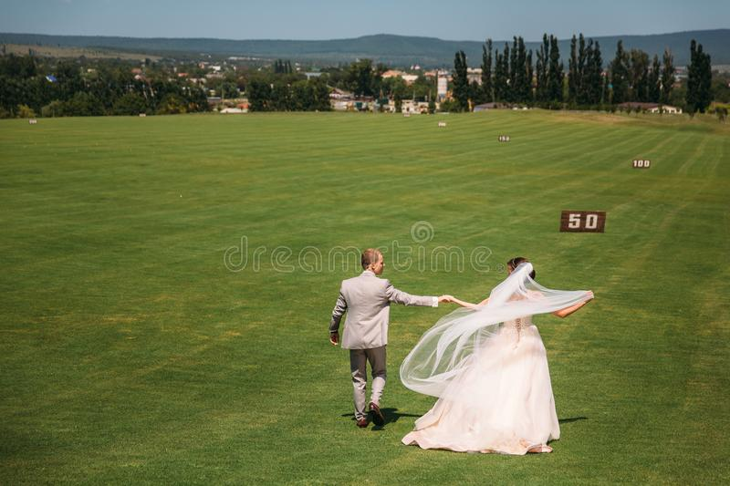 Rear view, newlyweds are walking along the green field of the golf club on a wedding day. The bride and groom in wedding. Dresses are holding hands. Man in a royalty free stock image