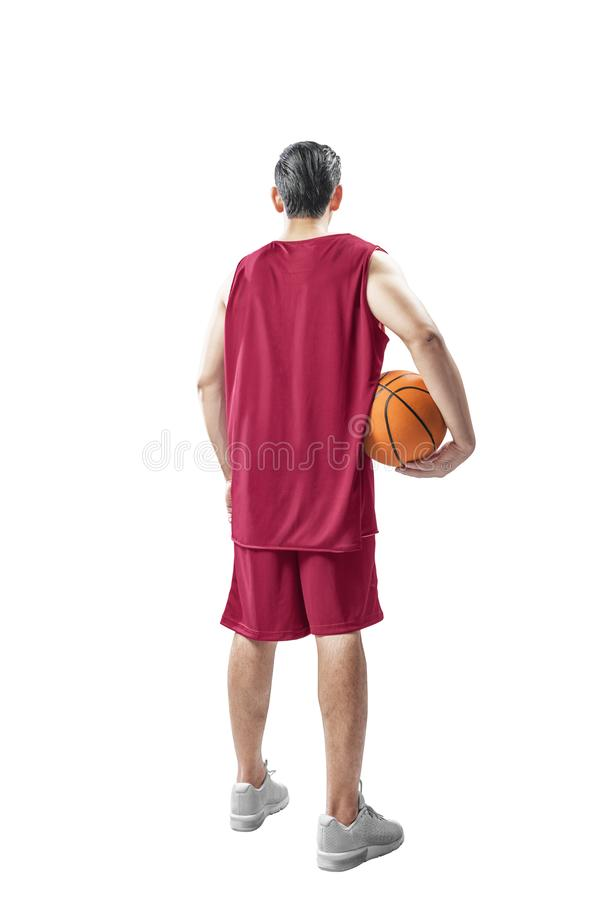 Free Rear View Of Asian Man In Basketball Uniform Holding The Ball Stock Images - 138720694