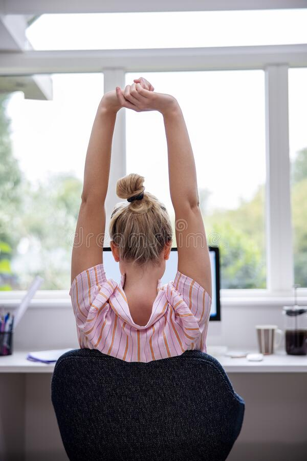 Free Rear View Of Woman Working From Home On Computer  In Home Office Stretching At Desk Stock Photo - 193870510
