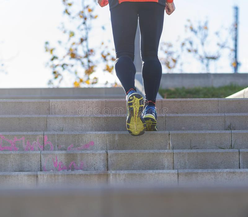 Rear view of one senior caucasian athlete man training running up and down the stairs outdoors in a park in a sunny day stock photo