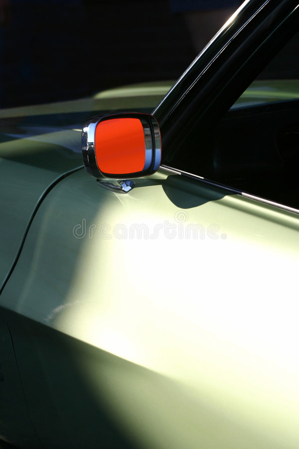 Rear View Orange. An external rear view mirror reflecting a orange color. This is indeed a classic car shown in a slightly abstract appeal royalty free stock images