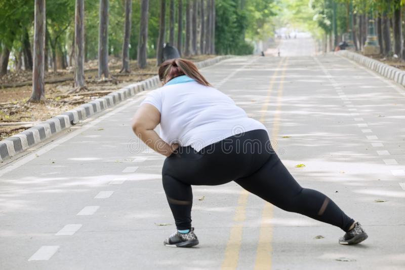 Overweight woman stretching her legs on road stock photo