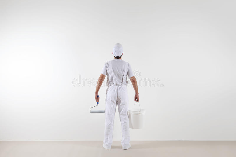 Rear view of painter man looking at blank wall, with paint roller and bucket, isolated on white room royalty free stock image