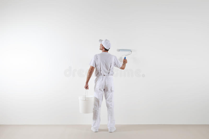Rear view of painter man looking at blank wall, with paint roller and bucket, isolated on white room royalty free stock photo